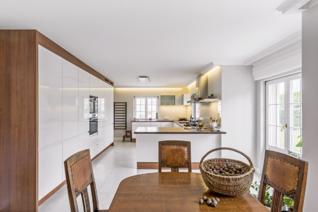 Kuchyňská linka ve tvaru písmene C vytváří na straně směrem k jídelnímu koutu praktický poloostrůvek. Ve vysokém nábytkovém modulu jsou vestavné spotřebiče, spížní skříně a velkorysé úložné prostory