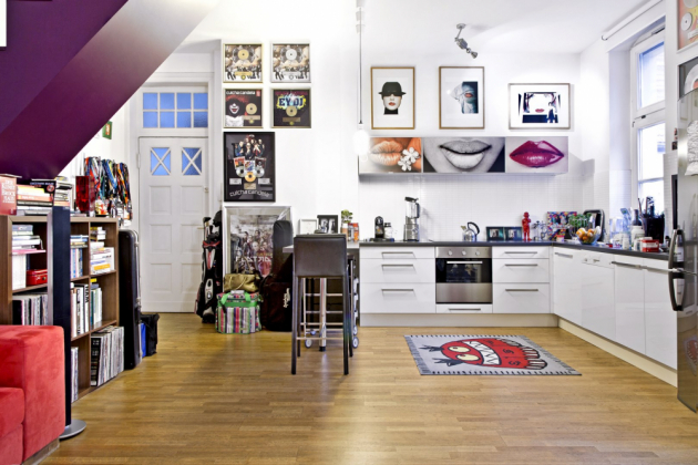 Bílá kuchyň se přirozeně včleňuje do obýváku. Spodní skříňky s prostornou pracovní deskou jsou pro majitele dostačující