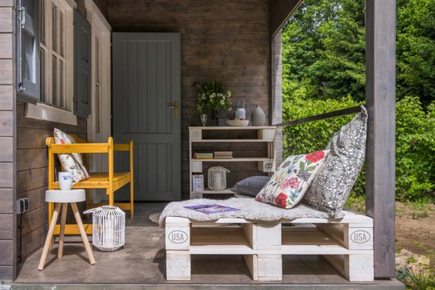 Terasa, na niž dopadá polední slunce, je velmi příjemnou součástí chaty. Zdobí ji nábytek a la palety a betonové doplňky, pocházející z Magdiny dílny