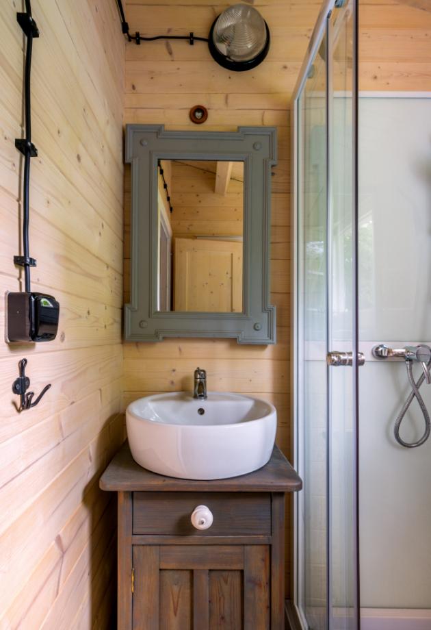 Do miniaturní koupelny se vešel sprchový kout, toaleta a umyvadlo posazené na nočním zrestaurovaném stolku. Zrcadlo má rám původem od popelnice