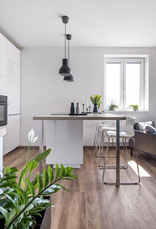 Místo velkého ostrůvku vybrali majitelé subtilnější řešení malého typu s větší dřevěnou deskou, která slouží jako jídelní stůl