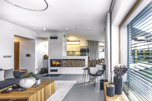 """V interiéru architekt rozehrál v rámci konceptu """"odebírání hmot"""" zajímavou situaci, kdy nábytek nebo krbové těleso buď vyrůstá, nebo naopak srůstá s hmotou domu, což je zároveň podpořeno použitými polyuretanovými stěrkami"""