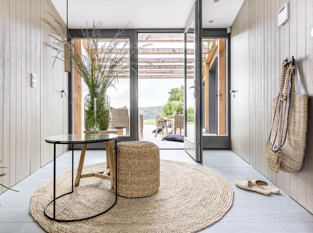CHODBA Na prostornou vstupní chodbu navazuje atrium, příjemně kryté v závětří. Posezení na terase zajišťuje ratanový nábytek (Tine K Home). Přátelský vzhled chodby dotvářejí prvky z mořské trávy a dalších přírodnin