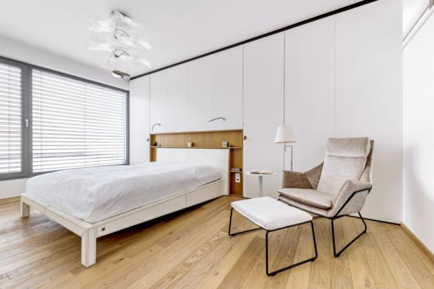 LOŽNICE Čistě aklidně působí ložnice sbílou postelí skoženým čalouněním. Bílá úložná stěna ukrývá dvě prostorné šatny
