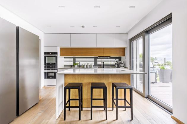 kuchyň Kuchyň navrhli podle majitelčiných představ architekti zKyzlink Architects. Je situovaná dojedné linie sprotilehlým ostrůvkem. Pracovní plochy abočnice ostrůvku jsou zumělého kamene