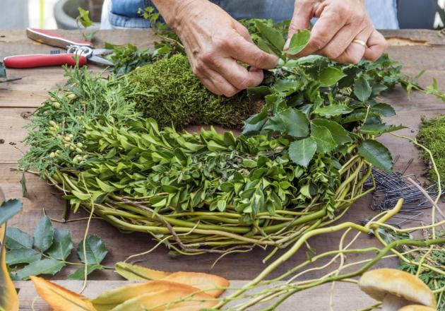 Ze zelených větviček si připravíme malé svazečky, které postupně floristickými sponami zapichujeme doslaměného korpusu. Stejně připevníme dospodní části mech.
