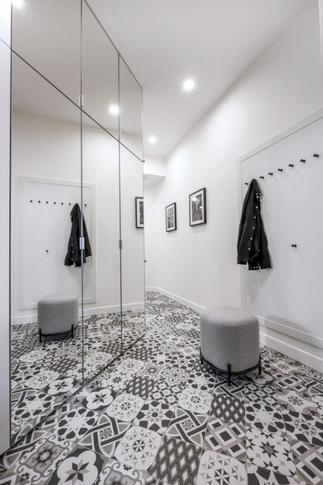 Černobílé ladění a zrcadlová dvířka vestavěných skříní činí z předsíně světlou a vlastně i vzdušnou místnost