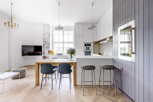 Obytný prostor Největší místností vbytě je kuchyň spojená sjídelnou aobývákem. Nábytek vkuchyni je bílý suzavřenými skříňkami nabízejícími dostatek úložného místa. Mosazný lustr zbyl popůvodních majitelích apaní domu mu dala nový lesk