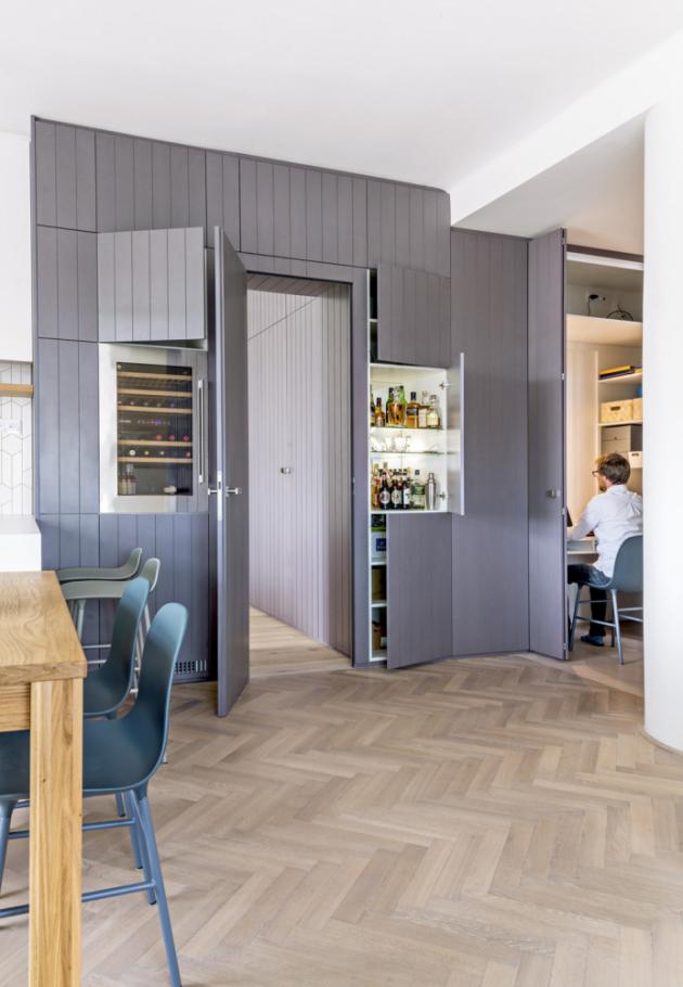 Obytný ipracovní prostor Multifunkční stěna je nosným designovým, ale ifunkčním prvkem celého bytu. Vhlavní obytné místnosti nabízí úložné skříňky, vinotéku, bar, pracovnu aschovává ivchod doložnice