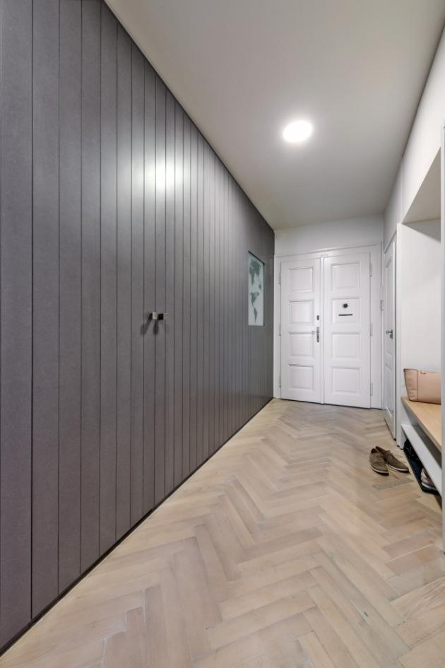 Šatna Multifunkční stěna vchodbě ukrývá iprostornou šatnu stechnickým zázemím. Před rekonstrukcí byla vtěchto místech kuchyň. Vbytě zůstala ipůvodní parketová podlaha adveře skováním. Porepasi jsou hezkými prvky, které ctí ducha staré zástavby