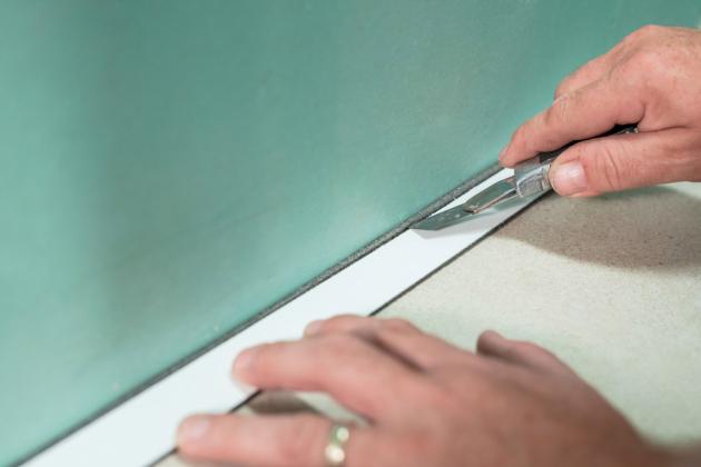 Dilatační pásku DSAT odřízneme ve výšce předpokládané hrany obkládačky nebo soklu.