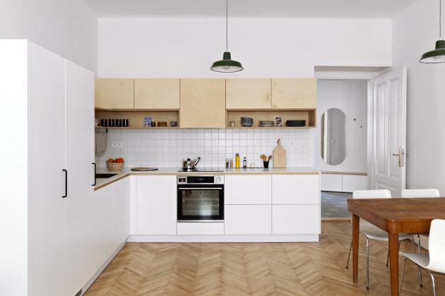 KUCHYŇSKÝ KOUT Součástí obytného prostoru je rohová kuchyň kombinující bílé plochy stříkané MDF desky a březovou překližku. Nabízí dostatečné úložné prostory i pracovní plochu