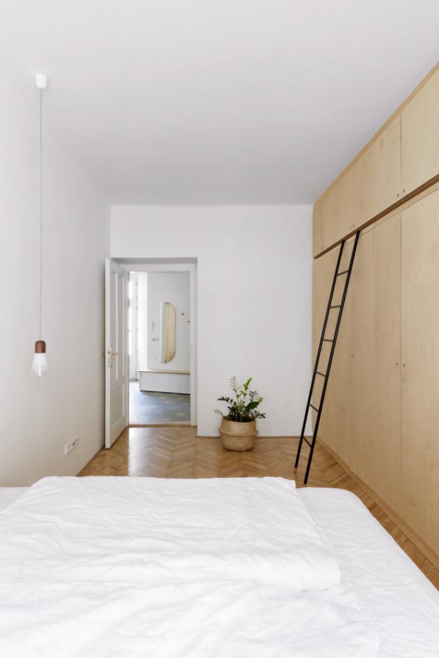 LOŽNICE Zastoupení překližky je asi nejvýraznější v ložnici, kde je z ní vyrobená vestavěná skříň a knihovna, táhnoucí se po celé jedné stěně, a také postel