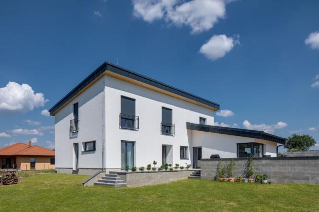 Dvoupodlažní dům spůdorysem ve tvaru písmene L a dvěma pultovými střechami je orientován do přilehlých polností, kde již není plánována další výstavba.