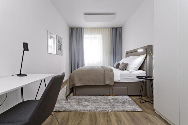 LOŽNICE Tlumené uklidňující barvy a komfortní postel od Ambience Design jsou hlavními prvky ložnice. Vešel se tam i minimalistický pracovní stůl a vysoká šatní skříň
