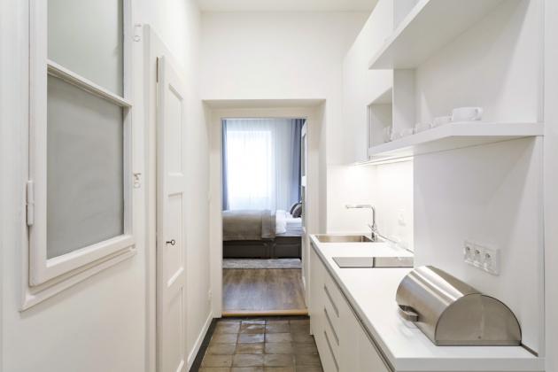 KUCHYŇ Kuchyň chtěl majitel zachovat v chodbě. Získala však kompletně nové zařízení a v bílé barvě působí vzdušně a nadčasově. Je vyrobená na zakázku