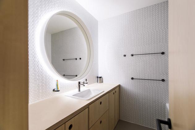 KOUPELNA Motiv kruhu se vtipně line celým interiérem, najdete ho na zrcadlech, úchytech či osvětlení. Překližku zde krásně doplňuje bílá šestiúhelníková mozaika, černé doplňky a baterie značky Grohe