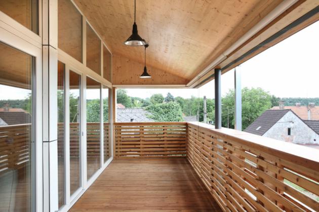 Nad úrovní přilehlé k silnici a směrem k výhledům do krajiny je prostorná krytá terasa, do které se kompletně otevírá celý obytný prostor nového domu.