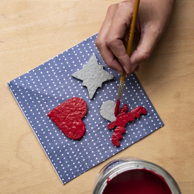 Poté si na ozdobách vytvořte své oblíbené motivy sčerveným a bílýmBalakrylem UNI. Až barvy zaschnou, pomocí široké jehly si opatrně vytvořte dírku a navlečte provázek.