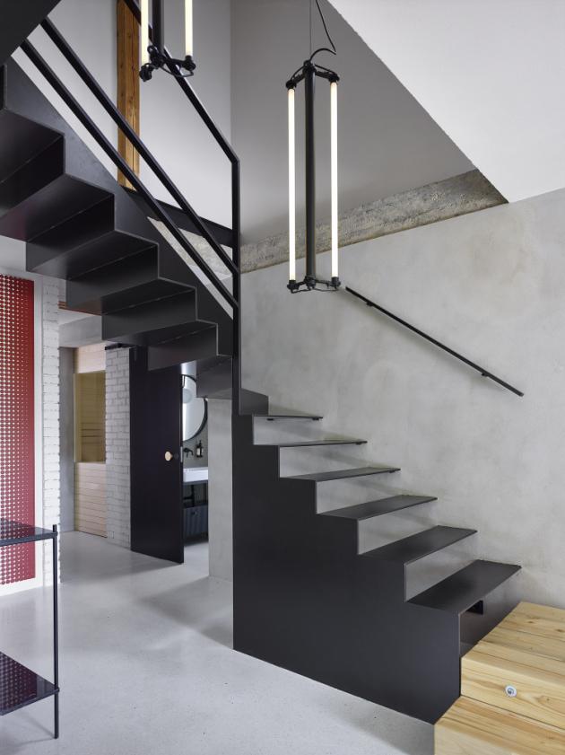 Černá ocel a přírodní dřevo (dubové podlahy jsou sladěné s barvou trámů) spolu se šedobílými štuky a omítkami spoluvytvářejí (troj)barevnou střízlivost interiéru.