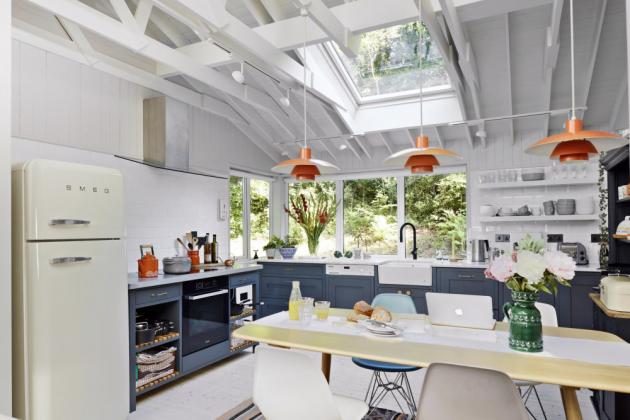 Kuchyňskou část otočenou k lesu prosvětluje střešní okno. Jídelní stůl s mramorovou deskou osvětlují stylové lampy PH 4/3 od Louis Poulsen