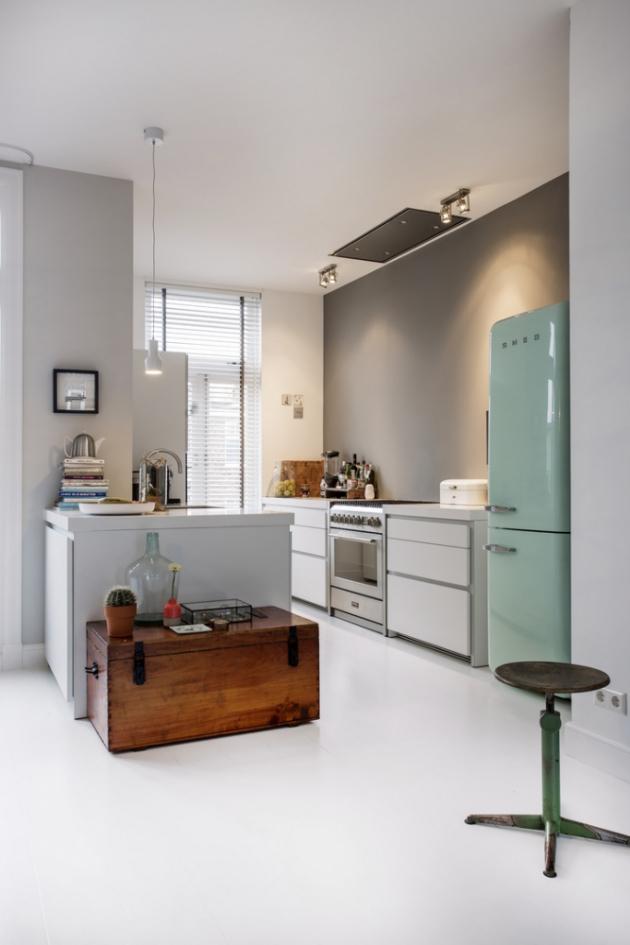 KUCHYŇ Bílá neutrální kuchyň v moderním stylu nechává vyniknout barevné retro lednici a staré dřevěné truhle