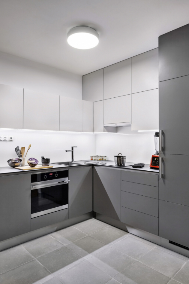 KUCHYŇ V čistě pánském stylu je šedá kuchyň, vyrobená na zakázku. Stěnu z betonářské výztuže vyrobil podle návrhu architektů sám majitel a dotvořil si i světlo nad jídelní stůl