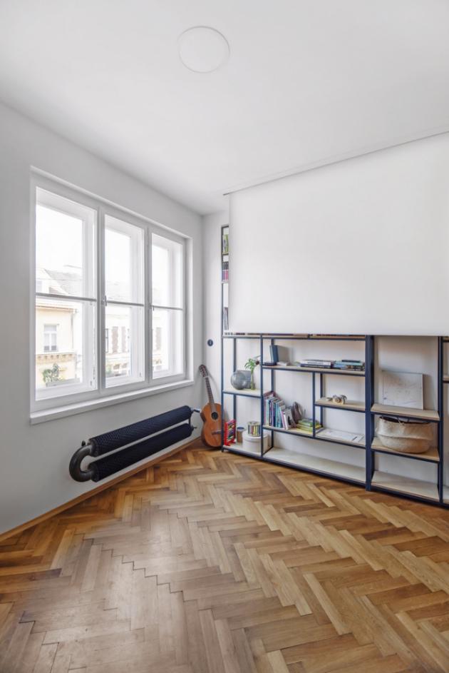 Železná konstrukce a dřevěné police tvoří knihovnu vyráběnou na míru. Televizi nahrazuje stahovací promítací plátno