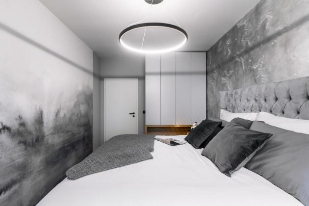 Autorskou tapetu s jemným vzlínajícím se akvarelem a betonovou stěrku s lehkou perletí doplňuje trochu měkkého luxusu v podobě vysoké kontinentální sametové postele, který majitelé velmi uvítali