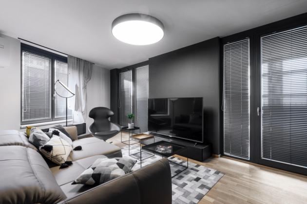 Přisazené stropní LED světlo od značky Halla o průměru 90 cm osvítí celou obývací zónu a zároveň nepůsobí dominantně. Světlo se stmívá do teplého až intimního odstínu barvy. Doplňuje ho stmívatelná stojací lampa značky Lunar