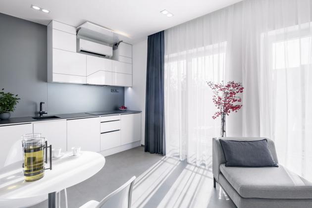 KUCHYŇ Na jednoduché bílé kuchyni se promítá motiv vyfrézované tmavě šedé linky. Zeď za kuchyní pokrývá šedé sklo, které také tvoří příčku mezi koupelnou a jídelnou (AGC Flat Glass Czech). V kuchyňské skříňce je vestavěná klimatizace, která byla v podkrovním bytě nutností
