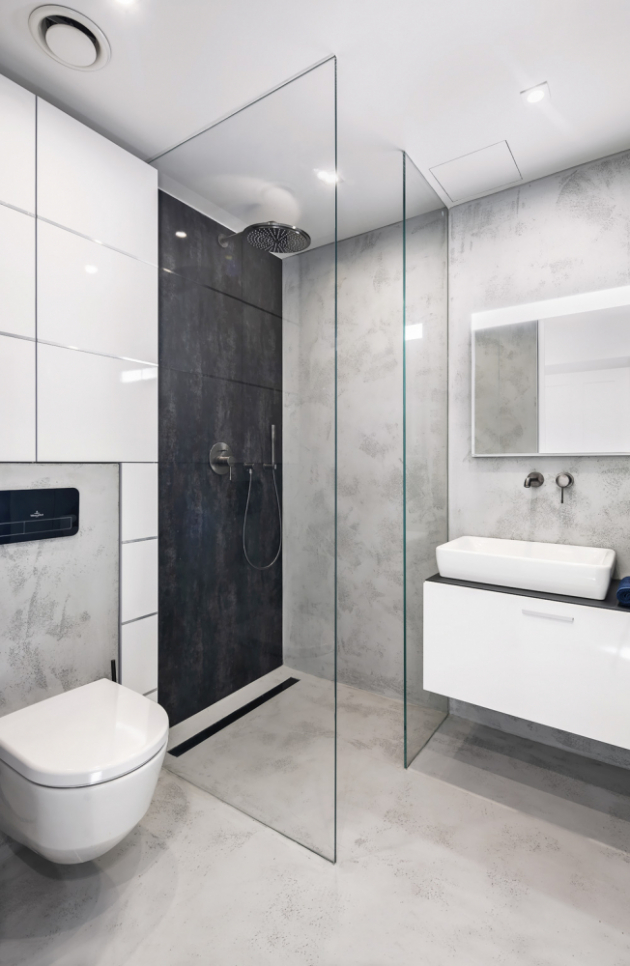 KOUPELNA Vzdušný dojem koupelny podtrhují skleněné zasunovací dveře. Designovým a zároveň praktickým prvkem koupelny jsou na míru vyrobené vestavěné skříňky vedle toalety. Sprchový kout je vymezen pouze skleněnou příčkou