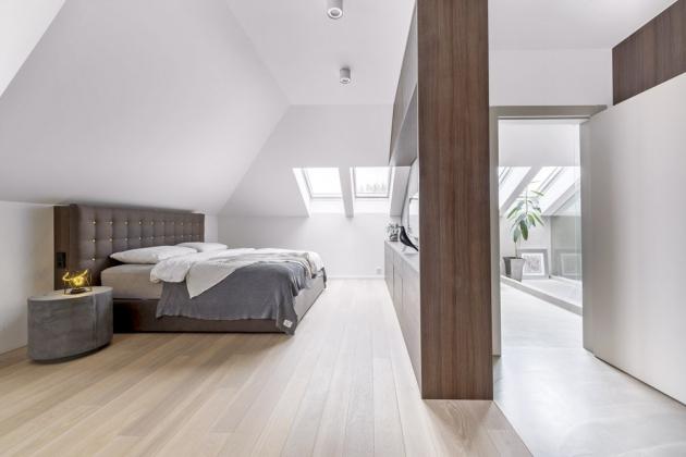 Manželská ložnice s vysokým čalouněným dvojlůžkem zabírá velkou část podkroví a je volně propojená s šatnou a koupelnou