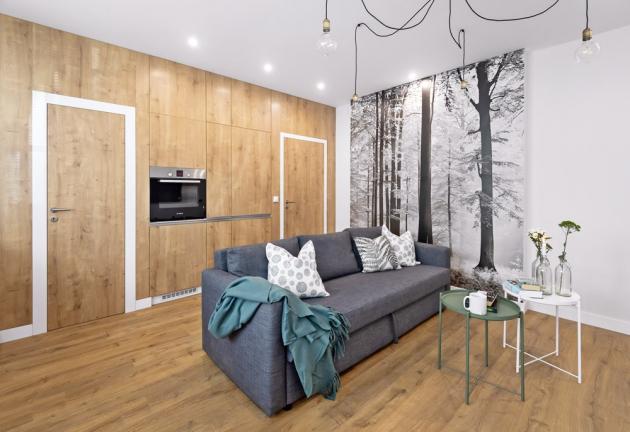 """OBYTNÝ PROSTOR Fototapeta lesa (www.e¬color.cz) je hezkou dominantou místnosti. Zajímavým detailem je také svítidlo """"pavouk"""" (www.svet¬svitidel.cz), sedačka a odkládací stolky jsou z IKEA"""