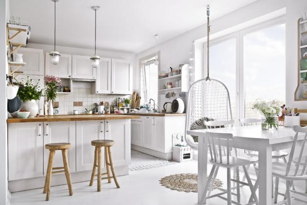 KUCHYŇ Bílá barva udala základní tón celému skandinávsky laděnému interiéru. Masivní dřevo v přírodním odstínu zahřívá a skvěle doplňuje studenou bílou