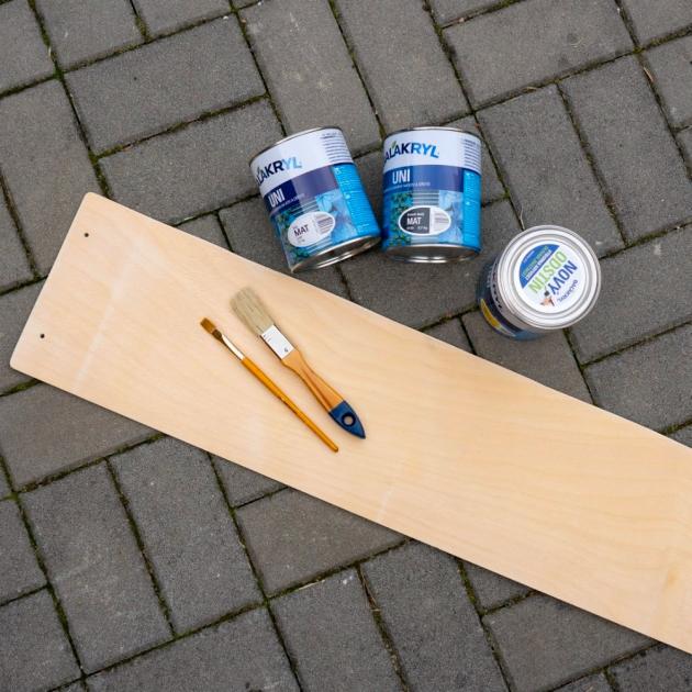 Na výrobu závěsného metru vám postačí dřevěná deska, která je kdostání vhobby marketech či obchodech pro kutily, a krycí barvy, které jsou vhodné na dřevo, zdravotně nezávadné a odolné vůči popraskání, např. Balakryl UNI. Zdesky vyřízněte pruh o šířce asi 20 cm a o délce přibližně 1 metr. Zjedné strany do metru navrtejte dva otvory pro zavěšení. Poté si připravte štětce a barvy a metr dle vlastního vkusu pomalujte.