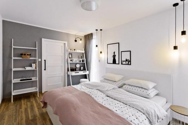 LOŽNICE Majitelka si přála do ložnice toaletku, tak to designérka vyřešila dvěma policemi a la žebřík z Bonami – jedna slouží jako toaletka, druhá jako knihovna. Bílá postel je pořízená v IKEA