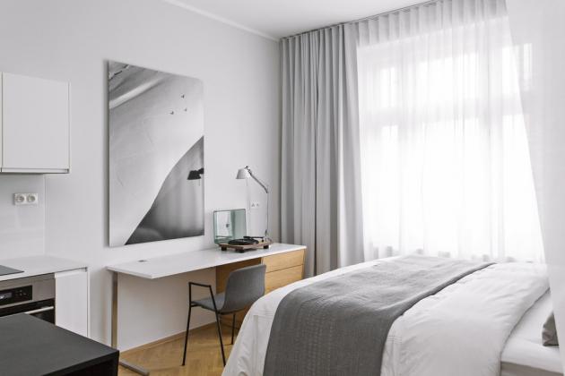 LOŽNICE Vysokou a prostornou postel s šedým čalouněním vyráběla pro Ambience Design na míru firma Situs. Matrace si dováží Ambience Design z Anglie