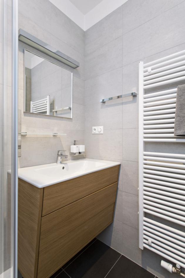 KOUPELNA Sprchový kout a umyvadlo posazené na zešikmené umyvadlové skříňce je dostatečný komfort, který potřebuje zaměstnaný muž v příležitostném bydlení