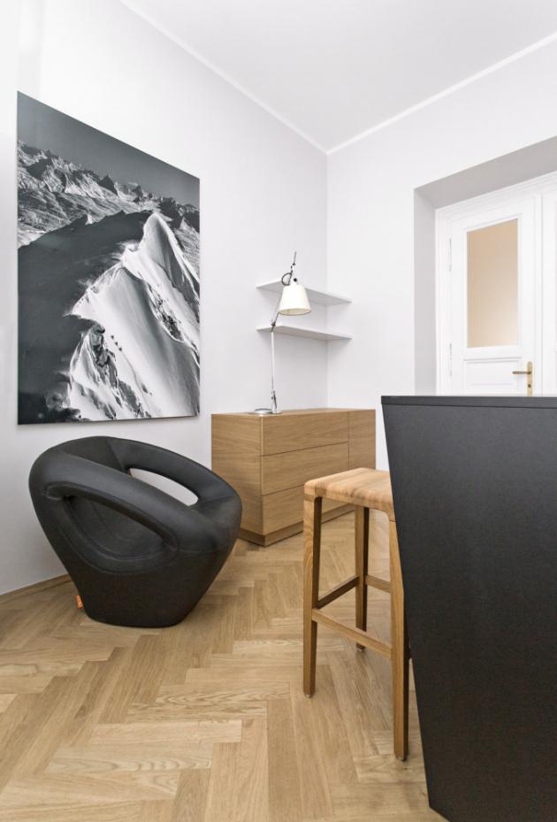 JÍDELNA Jídelní stůl nahrazuje zešikmený ostrůvek vyráběný na zakázku ze speciálního ekologického materiálu. Opticky celou místnost zvětšují velkoformátové fotografie z limitované edice fotografa Marka Fishera. Drobný nábytek je od firmy TOJO