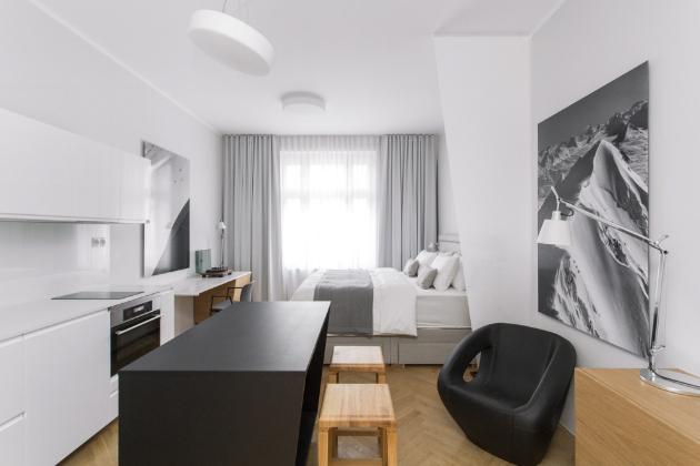 OBYTNÝ PROSTOR Celé ladění interiéru vychází z kombinace bílé a šedé barvy a z odstínu dubu. Zajímavým prvkem je zešikmený úhel, který se v bytě několikrát opakuje na nábytku a na zástěně, decentně oddělující postel od obytné části místnosti