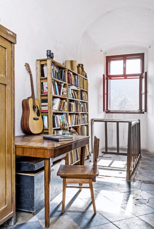 Za zábradlím v přízemní chodbě jsou v podlaze dřevěné dveře ukrývající schodiště vedoucí do zahrady