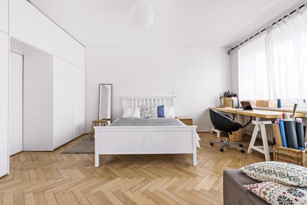 LOŽNICE Velký pokoj s postelí a vestavěnými skříněmi slouží jako ložnice a domácí kancelář s velkým pracovním stolem