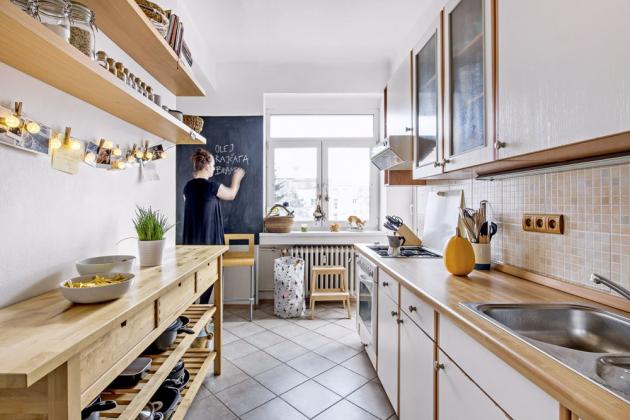 KUCHYŇ Částečným ubouráním zdi mezi kuchyní a pokojem vznikl dostatečně velký průchod na to, aby měl člověk v kuchyni spojení i s lidmi v obýváku. Část zdi je pokrytá tabulovou barvou, kterou si majitelka splnila jeden ze svých snů