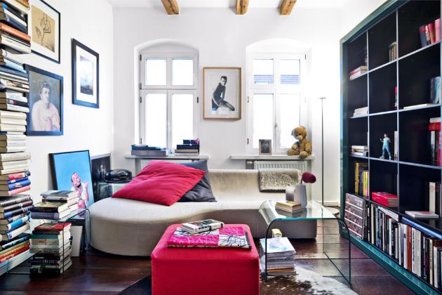 OBÝVACÍ POKOJ Velké množství knih dělá v bytě další zajímavou kulisu. K odpočinku je vždy připravené menší šedé sofa a červený taburet