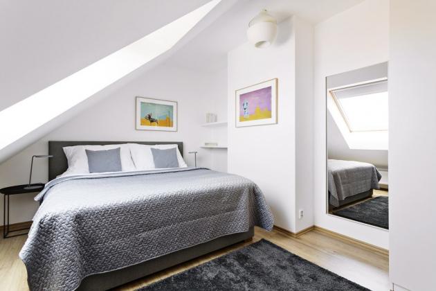 LOŽNICE Ložnice je laděná do neutrálních uklidňujících barev. Vysoká postel s polstrovaným čelem je z portfolia Ambience Design, doplňuje ji vysoká anglická matrace