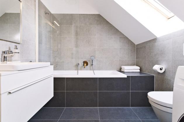 KOUPELNA Velkoformátové obklady ve dvou odstínech souzní s celým interiérem. Kompromis mezi sprchovým koutem a vanou řeší vanová zástěna