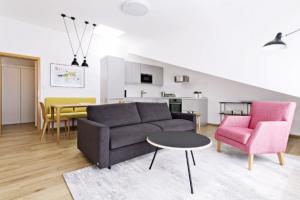 OBYTNÝ PROSTOR V střešní nástavbě staršího činžovního domu vznikl moderní světlý byt pro mladý manželský pár. Dekory dřeva doplňují neutrální tóny i svěží barvy