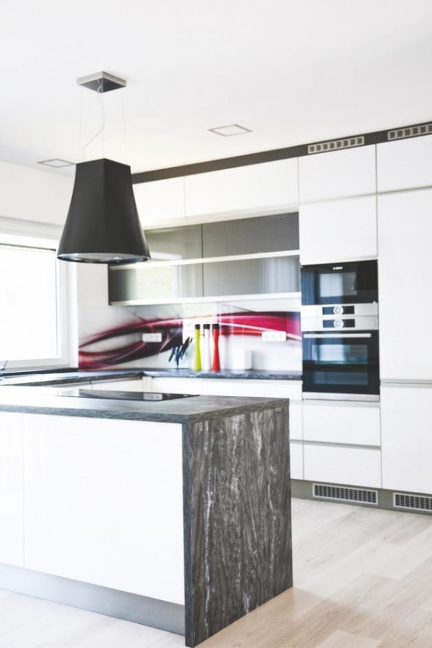 Pro řešení otevřené kuchyně sáhla majitelka po bílo-šedivých nábytkových dvířkách ve vysokém lesku, doplněné pracovní deskou vimitaci šedého mramoru. Chytrým řešením kuchyňské linky je volný přechod pracovní linky svarnou deskou do prostoru, díky čemuž má majitelka při vaření výhled do jídelny iobývacího pokoje. Vysoce designová je i závěsná digestoř, jež působí zcela přirozeným dojmem lustru.
