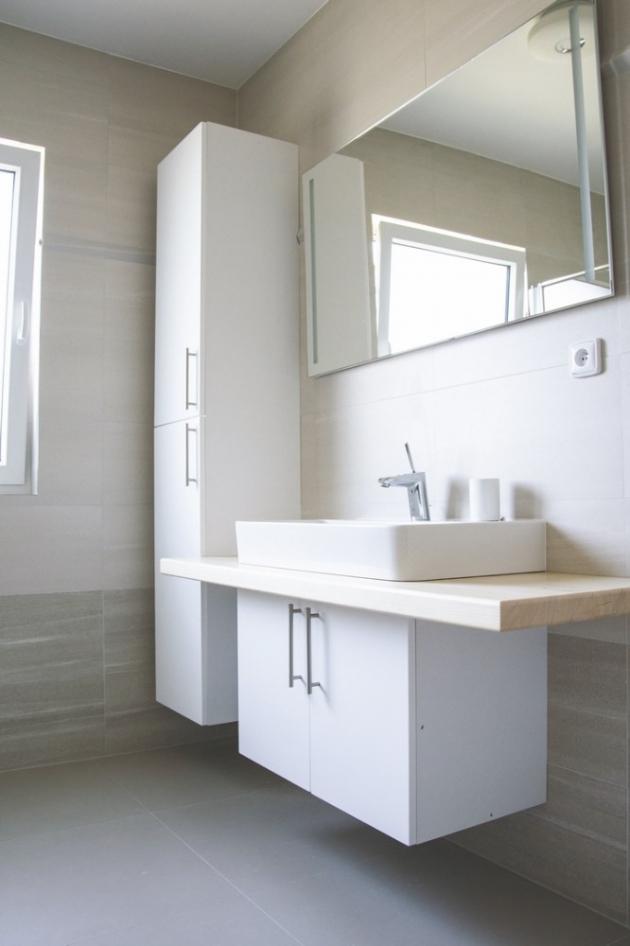 Koupelna s WC, jejíž obklady, dlažbu isanitární zařízení si majitelé přáli vybrat sami, je taktéž laděna do bílých barev. Nábytková dvířka vkombinaci spřírodním dřevodekorem na desce pod umyvadlem a lehce šedá dlažba přechází vbéžový kachlový obklad, čímž se místnost opticky zvětšuje.